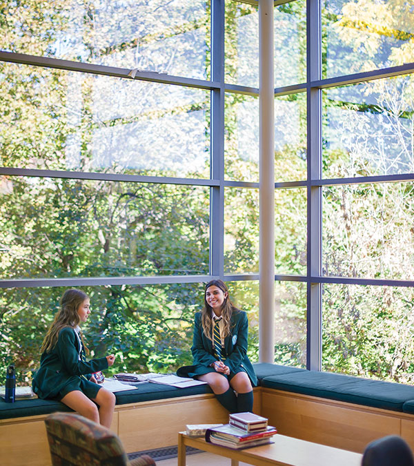 Two students sitting in front of windows with trees in the background.