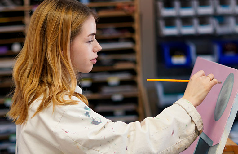 Upper School student painting at an easel