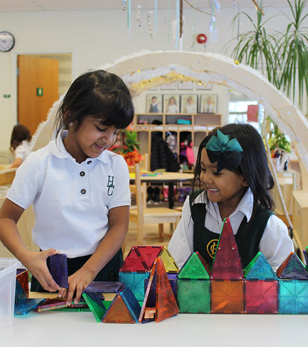 Two Kindergarden students play with coloured blocks.